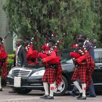 South Africa's President Jacob Zuma arrives by car for a meeting with Nigerian President Muhammadu Buhari at the Presidential villa in Abuja, on Tuesday as the ceremonial band corps precedes him. | AFP-JIJI