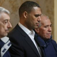 In this photo taken Sunday, Gino Pollicardo (left) and Filippo Calcagno (right), two Italian nationals who were held hostage in Libya, arrive at Mitiga airport, about 8 km east of Tripoli, where they were met by Libyan officials.   AP