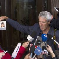 Anthony Foster, member of the Australian group of relatives and victims of priestly sex abuses, shows reporters the photo of his two daughters, who were both abused by the same priest and one of them later committed suicide, outside of the Quirinale hotel after their meeting with Australian cardinal George Pell, in Rome, Thursday. | AP