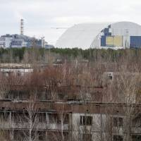 A containment shelter for the damaged fourth reactor (left) and the New Safe Confinement (NSC) structure (right) at the Chernobyl Nuclear Power Plant are seen from Ukraine's abandoned town of Pripyat Wednesday. | REUTERS