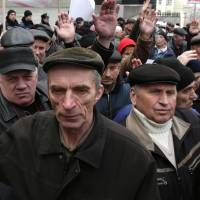 Former personnel who dealt with the Chernobyl nuclear disaster vote for a resolution during a rally in front of Ukrainian Cabinet of the Ministers in Kiev on Wednesday. The protesters demand the restoration of their social benefits and entitlements, which have been canceled by the government of Arseniy Yatsenyuk and the previous governments. | AFP-JIJI