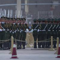 Chinese paramilitary police march during a flag-raising ceremony outside the Great Hall of the People on Tiananmen Square ahead of the opening of the National People's Congress in Beijing on Saturday. | AP