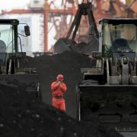 A front-end loaders shift coal imported from North Korea at a port in the Chinese border city of Dandong, Liaoning province, in this 2010 file picture. | REUTERS