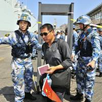 Chinese People's Liberation Army Navy personnel guide Chinese citizens boarding a naval ship at a port in Aden, in this March 2015 file photo. China has launched an unusual charm offensive to explain its first overseas naval base in Djibouti, seeking to assuage global concerns about military expansionism by portraying the move as Beijing's contribution to regional security and development. | REUTERS
