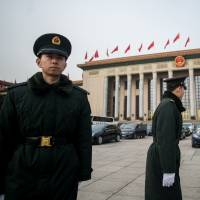 Security guards patrol outside the Great Hall of the People in Beijing during the second day of the National People's Congress on Sunday. | AFP-JIJI