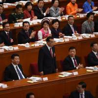 Chinese Premier Li Keqiang (standing) is applauded after delivering a report at the opening session of the National People's Congress held in the Great Hall of the People in Beijing on Saturday. President Xi Jinping is seen to his left. | AFP-JIJI