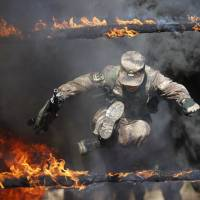 A Chinese People's Liberation Army soldier jumps through a flaming ring during a training session in Heihe, Heilongjiang province, on Saturday. | REUTERS