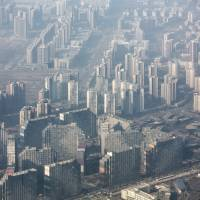 Buildings are shrouded by a cloud of smog in Beijing on March 2. | BLOOMBERG