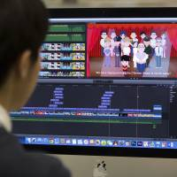 A video editor reviews an animated political cartoon while working at the Xinhua All-Media Service in the newsroom of China's official Xinhua News Agency in Beijing on Feb. 24. | AP