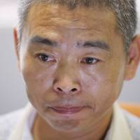 Chinese asylum seeker Dong Junming pauses during an interview in Bangkok on March 11. Dong, a practitioner of the Falun Gong spiritual movement, which is banned in China, was among nine Chinese asylum seekers who attempted a risky sea voyage to New Zealand but turned back after their boat was lashed by violent seas. | AP