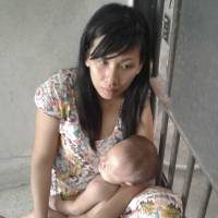 Gu Qiao holds her 1-year-old child, Li Yusheng, at a police station in southern Thailand's Chumphon province on March 3, after a failed attempt to reach New Zealand by boat. | AP