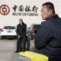 Men sit outside the Bank of China headquarters in Beijing on Feb. 25. Convicted con man Gilbert Chikli is credited with masterminding a type of fraud that has cost major multinational firms $1.8 billion over just two years. Chikli said he laundered 90 percent of cash through China and Hong Kong. Police traced tens of thousands of dollars in transfers from Chikli front companies to Bank of China accounts. | AP