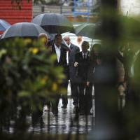U.S. President Barack Obama (center, left) arrives in the rain for a walking tour with historian Eusebio Leal (center, right) in the Vieja Havana neighborhood of Havana Sunday. | REUTERS
