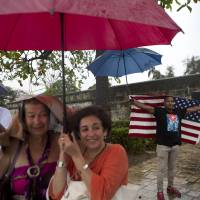 A handful of Cubans gather along the Malecon seawall under a steady rain to wave to U.S. President Barack Obama's convoy as it arrives in Old Havana, Cuba, Sunday. Obama's trip is a crowning moment in his and Cuban President Raul Castro's ambitious effort to restore normal relations between their countries. | AP