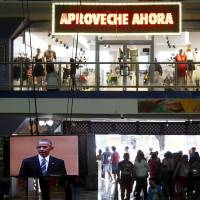 U.S. President Barack Obama is seen on a television screen at a shopping mall with a promotional sign reading 'Grab the opportunity' in Havana Monday. | REUTERS