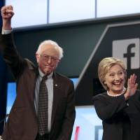 Democratic U.S. presidential candidates Sen. Bernie Sanders and Hillary Clinton wave before the start of Wednesday's debate in Kendall, Florida. | REUTERS