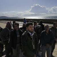 Migrants wait in the eastern Greek island of Samos after they were rescued while trying to cross in a dinghy the Aegean Sea between the eastern Greek Island of Agathonisi and the nearby Turkish shores, Thursday. Sixty-three members of the Yazidi community, all in one dinghy, were rescued and were taken to Samos. | AP