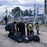 Migrants and refugees prepare their luggage after crossing the Greek-Macedonian border near the town of Gevgelija on Thursday, the day EU President Donald Tusk issued a blunt warning to economic migrants not to come to Europe, and chastised EU countries that have taken unilateral action to tackle the crisis. | AFP-JIJI