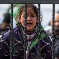 A migrant girl cries as she waits at a Turkish coast guard station at the Dikili district in Izmir Sunday. | AFP-JIJI