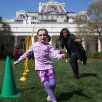First lady Michelle Obama cheers on children as they run through an obstacle course race in the Rose Garden of the White House in Washington Monday during the White House Easter Egg Roll. | AP