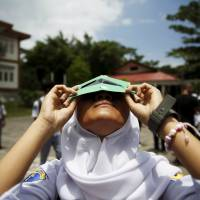 A student tests a self-made filter and looks at the sun after a joint workshop between the Hong Kong Astronomical Society and Indonesia's National Institute of Aeronautics and Space (LAPAN) at a high school on Ternate island, Indonesia, ahead of Wednesday's solar eclipse. | REUTERS