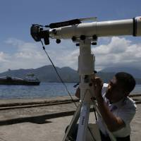 A staffer of the Indonesian Agency for Meteorology, Climatology and Geophysics (BMKG) prepares a lens to record a solar eclipse at the beach of Ternate Island, Indonesia, Tuesday. | REUTERS