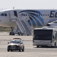 A bus carries away passengers from the hijacked EgyptAir aircraft after it landed at Larnaca airport Tuesday in Cyprus. | AP
