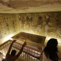 Tourists look at the tomb of King Tut as it is displayed in a glass case at the Valley of the Kings in Luxor, Egypt, in a file photo taken on Nov. 5, 2015. Egypt's Antiquities Minister Mamdouh el-Damaty said Thursday that analysis of scans of King Tut's burial chamber has revealed two hidden rooms that could contain metal or organic material. | AP