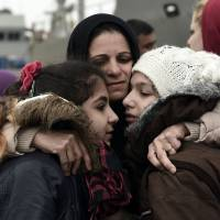Deniz Sidour, a Syrian Kurd from Aleppo, hugs her daughters as they are reunited in Mytilene, on the Greek island of Lesbos, on Tuesday after being separated while crossing from Turkey. | AFP-JIJI
