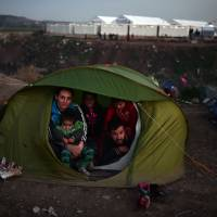 A family sits in their tent near of the Greek-Macedonian border, near the Greek village of Idomeni, on March 2. | AFP-JIJI