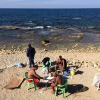 Lebanese men play cards and smoke a water pipe as they sunbathe during unusually warm weather at the Mediterranean Sea off the Corniche, or waterfront promenade, in Beirut on Feb. 9. | AP