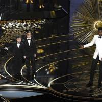 Oscars host Chris Rock gestures to Asian-American boys portraying auditors in a skit on Feb. 28 at the Dolby Theater in Los Angeles. | CHRIS PIZZELLO/INVISION/AP