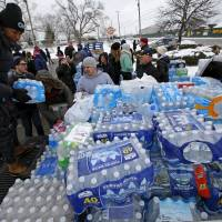 Volunteers distribute bottled water to help combat the effects of the crisis when the city's drinking water became contaminated with dangerously high levels of lead in Flint, Michigan, Saturday. | REUTERS