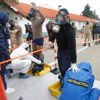 Volunteers train for a chemical attack at the Police National School of Nimes, southern France, Thursday. Law enforcement bracing for the European soccer championship are expected to train later with a fake explosion reminiscent of the suicide attacks on the French national stadium that night. The Nov.13 attacks began at the Stade de France stadium with three suicide bombers. | AP