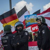 This file photo taken April 26, 2014, shows activists from the far-right National Democratic Party behind a police line in Berlin. | AFP-JIJI