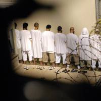 f gitmo-c 20160314 A group of detainees observe morning prayer before sunrise inside Camp Delta at Guantanamo Bay naval base in 2009. | REUTERS/DOD/PETTY OFFICER 2ND CLASS MARCOS T. HERNANDEZ / HANDOUT VIA REUTERS