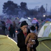 A man holds a child near the northern Greek border station of Idomeni Thursday. Thousands of refugees and migrants wait on the border between Greece and Macedonia and about 30,000 refugees and other migrants are stranded in Greece, with 10,000 at the Idomeni border crossing to Macedonia. | AP