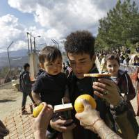 A migrant child receives an orange while being carried by a relative waiting for food outside the registration and hospitality center, known as a hotspot, on the eastern Greek Island of Samos, on the Aegean Sea,Thursday. Only children receive an orange each. Food is cooked daily by a group of women volunteers, all Samos' residents, as there is no provision by the authorities for food at the hotspot and migrants rely on private donations for food. | AP