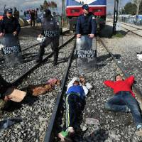 People sit and lie on train tracks and in front of Greek policemen during a protest of migrants and refugees to call for the opening of the borders, blocking a train coming from Macedonia in a makeshift camp at the Greek-Macedonian border near the Greek village of Idomeni Thursday. EU President Donald Tusk on March 3 issued a stark warning to economic migrants not to come to Europe, as he castigated countries for taking unilateral action to tackle the crisis. | AFP-JIJI
