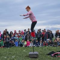 Children watch a performance by a volunteer entertainer near the northern Greek border station of Idomeni Thursday. | AP
