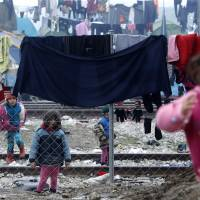 Refugee children play between clothes hung out to dry on fences and wires in a makeshift camp at the northern Greek border post of Idomeni, Wednesday. | AP