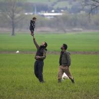 A man plays with a baby while walking in a field at the northern Greek border point of Idomeni Wednesday. Leaders of the EU's 28 divided nations plan to reconvene in Brussels this week in hopes of ironing out disagreements on a proposed agreement with Turkey in the migrants crisis. | AP