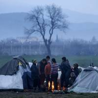 Migrants try to warm themselves next to a fire, between tents in a makeshift camp at the northern Greek border post of Idomeni, as the border fence and buildings from the southern Macedonian town of Gevgelija are seen in the background Wednesday. | AP