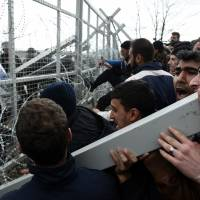 Refugees and migrants try to break an iron fence from the Greek side of the border as Macedonian police stand guard, near the northern Greek village of Idomeni on Monday. Macedonian police fired tear gas and stun guns Monday as several hundred Iraqi and Syrian refugees, frustrated at days of delays in crossing the Greek-Macedonian border, broke down a gate on a nearby rail crossing. | AP