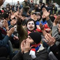 Stranded refugees and migrants shout slogans as they protest at the Greek-Macedonian border near the northern Greek village of Idomeni on Monday. | AP