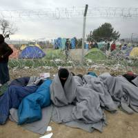 Refugees and migrants who entered Macedonia illegally and were detained by the police wait to be returned to Greece at a checkpoint on the border line near southern Macedonia's town of Gevgelija, Monday. | AP