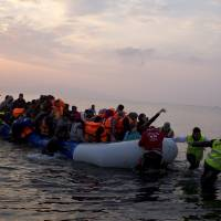Volunteers help migrants and refugees on a dingy as they arrive at the shore of the northeastern Greek island of Lesbos, after crossing the Aegean sea from Turkey on Sunday. In another incident two Syrian refugees have been found dead on a boat on the first day of the implementation of an agreement between the EU and Turkey on handling the new arrivals. | AP