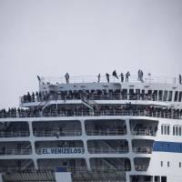 Refugees and migrants are seen on board the Eleftherios Venizelos passenger ferry as they are transferred to the Greek mainland, following their departure from the port of Mytilene on the Greek island of Lesbos, Sunday. | REUTERS