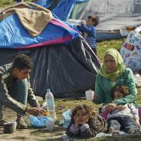 A migrant family rests near the border that separates the Greek side from the Macedonian one to be allowed to cross into Macedonia, at the northern Greek border station of Idomeni, Sunday. A regional governor called on the Greek government Saturday to declare a state of emergency for the area surrounding the Idomeni border crossing where thousands of migrants are stranded due to border restrictions along the route toward Western Europe. | AP