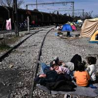 People rest by a rail track on Sunday in the makeshift camp at the Greek-Macedonian border near the village of Idomeni where thousands of migrants and refugees are stranded. | AFP-JIJI